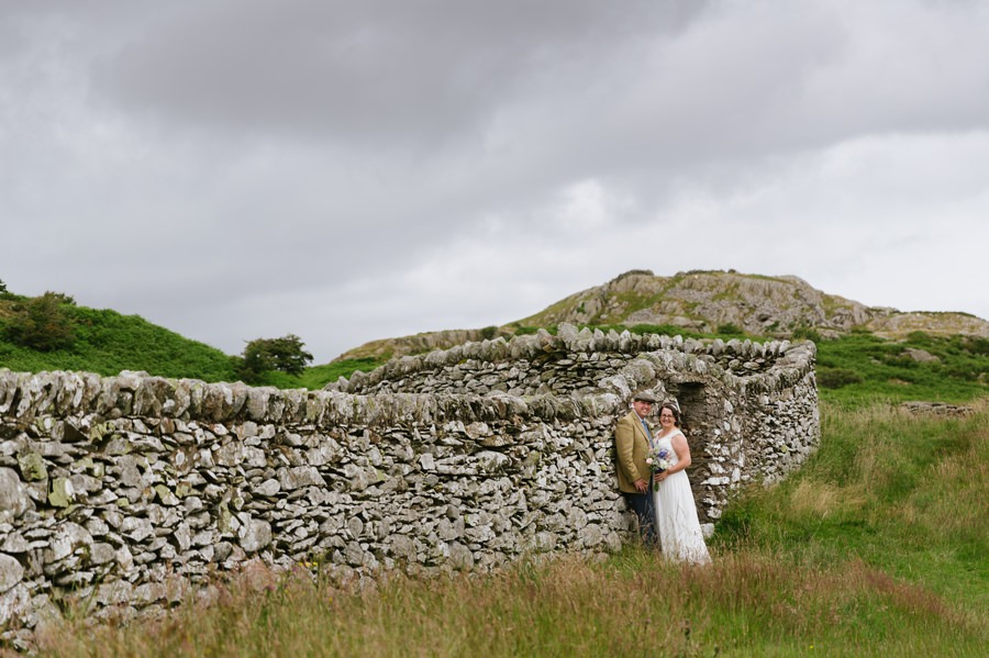 bride and groom with stone wall near Conwy Get married in North Wales