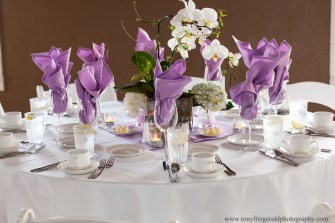 purple table decorations and white orchids at wedding