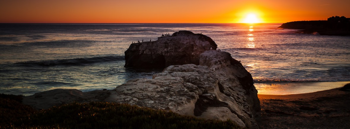 Sunset at Natural Bridges in Santa Cruz California with the sun dipping into the ocean