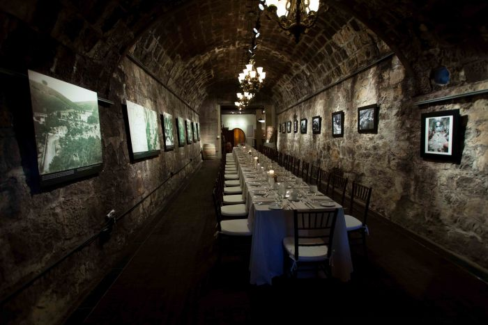 Testarosa winery cave with table setting and wine barrel.
