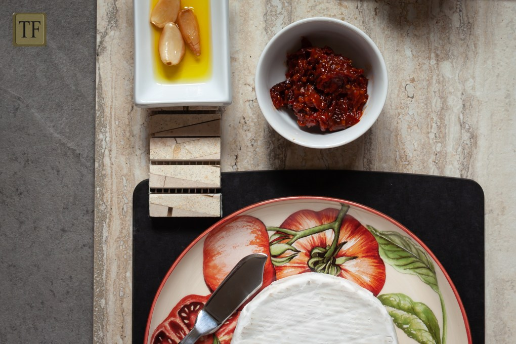 garlic confit, dried tomatoes, tomato paste and brie on plates