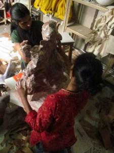 Sajida and Sunita work to cover it in papier mache.