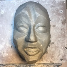 A rough sculpt in clay of one of the masks.