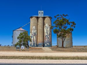 Photo of three silos in a field with artwork painted on them
