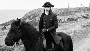 Good looking man, riding horse in Regency 18th Century Poldark Costume with stormy sky, tin mine ruins and Atlantic ocean in background