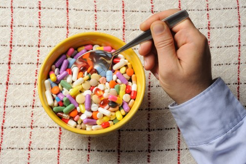 Bowl filled with pills and hand with spoon on a table