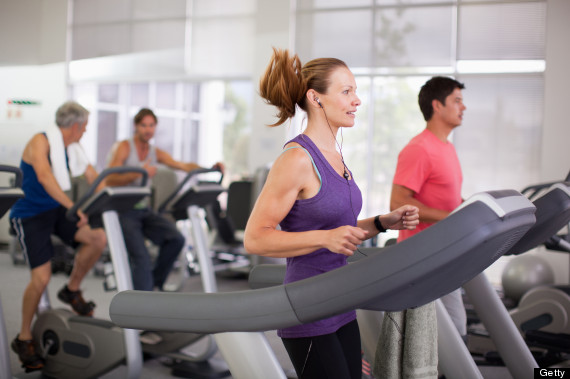Portrait of smiling woman on treadmill in gymnasium