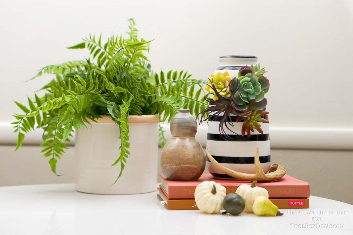 modern fall vignette with orange books and black and white striped vase with succulents