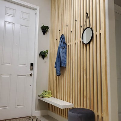 DIY wooden 1x2s added to the wall for coats with a bench