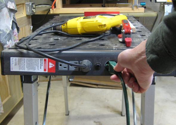 Plugging a cord into the workbench