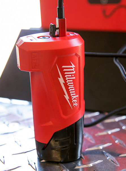 Milwaukee M12 Battery and Phone Charger Plugged in for Charging