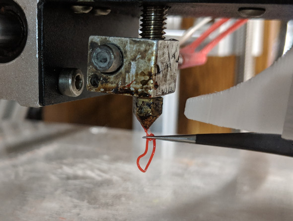 Using tweezers to clean filament off a hot end