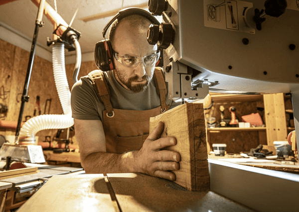 worker cutting wood using best resawing bandsaw