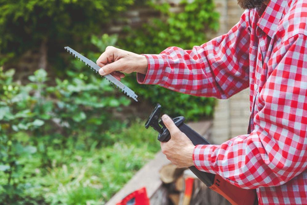Man Changing Cordless Reciprocating Saw Blade
