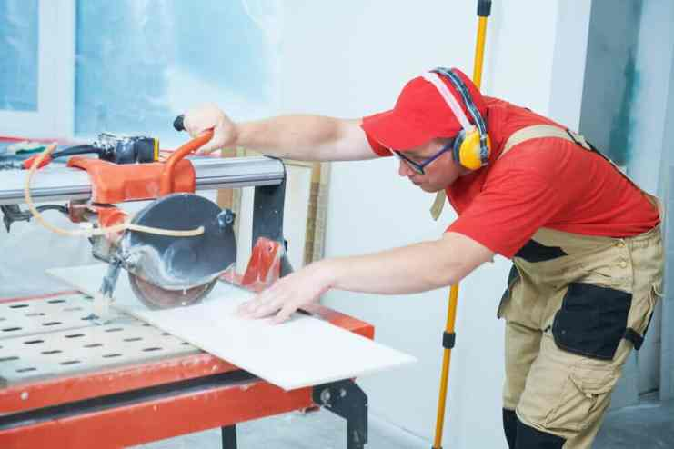 A man oparate a wet tile saw machine to cutting tile