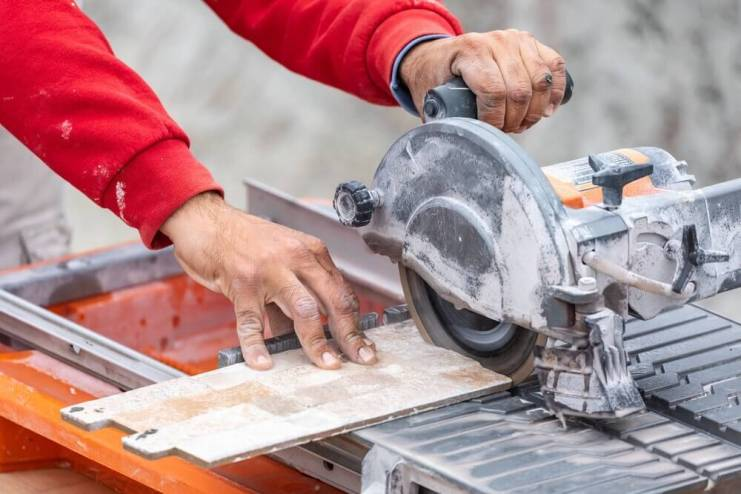 Worker Using Wet Tile Saw to Cut Wall Tile