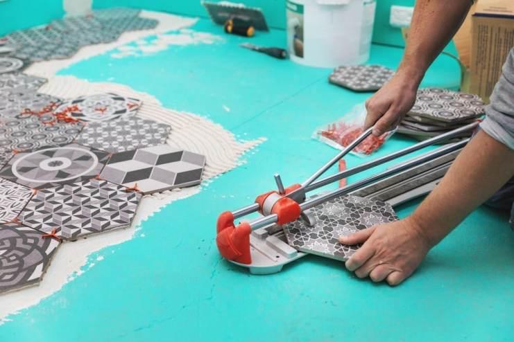 Tiler cutting tile with manual tile cutter