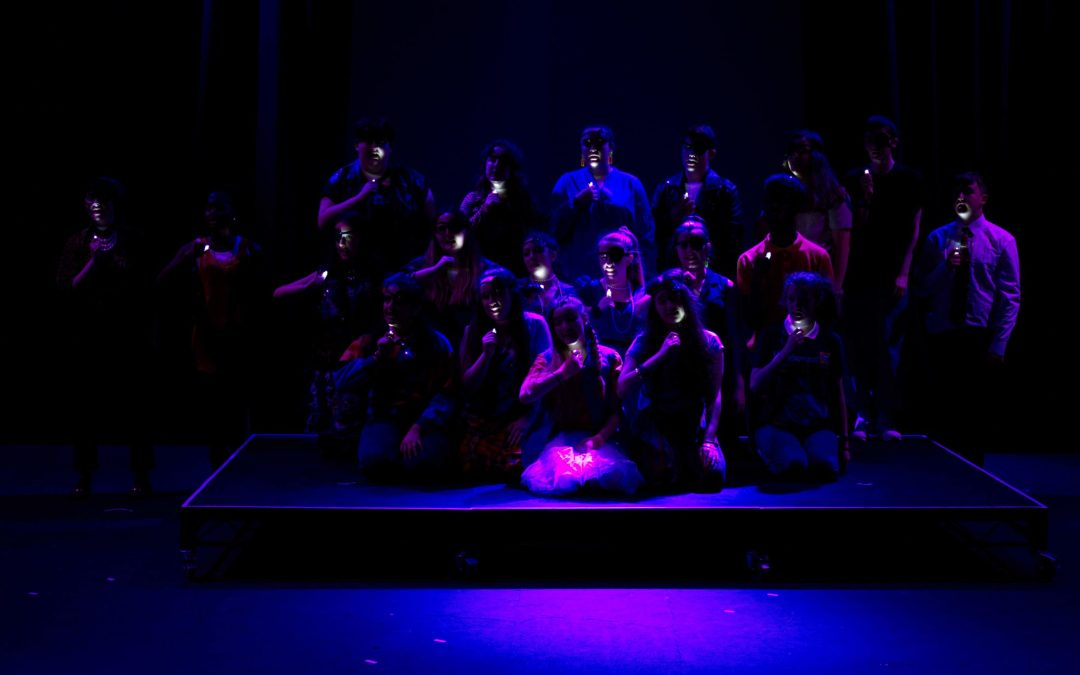 Choir of young people on their knees on a dark stage with tiny white lights held to their face.