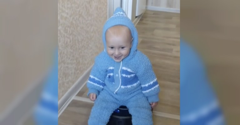 Toddler rides robot vacuum cleaner