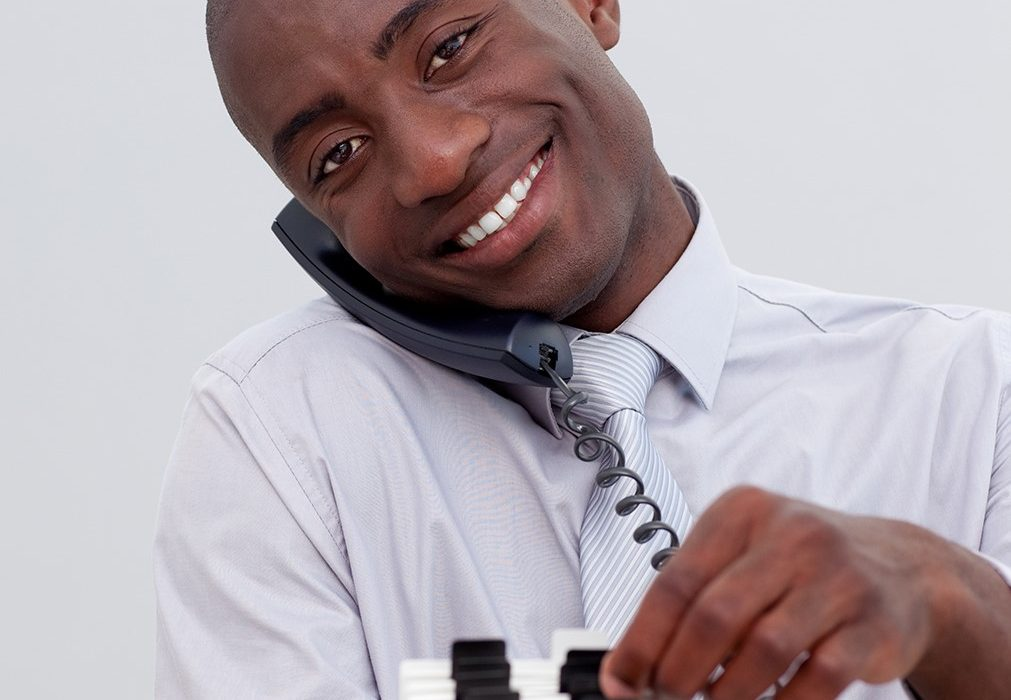 Afro-American businessman on phone searching for an index holder