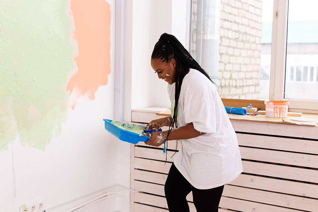 Repair in the apartment. Happy young woman paints the wall with paint