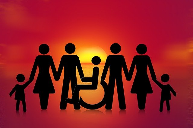 Symbols of people holding hands, including one in a wheelchair, representing how TOPDOG Legal Marketing can help you understand the importance of having an ADA accessible law firm website.