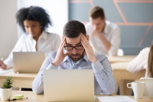 frustrated worried male employee reading news, tired exhausted office worker feeling headache at work