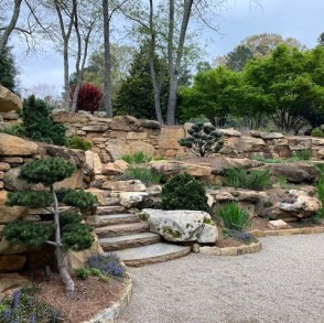Tiered rock garden with different conifers, topiary, and color