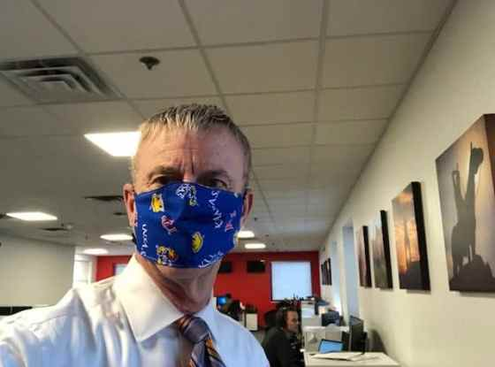 Journalist John Holt using a mask from the University of Kansas while at his work as an anchor and reporter, sharing his career opportunities