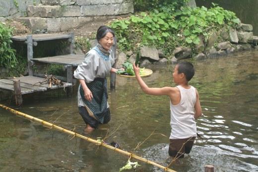 阿嬤教昭廣在河上橫放一支竹竿撈起上游漂來的蔬果