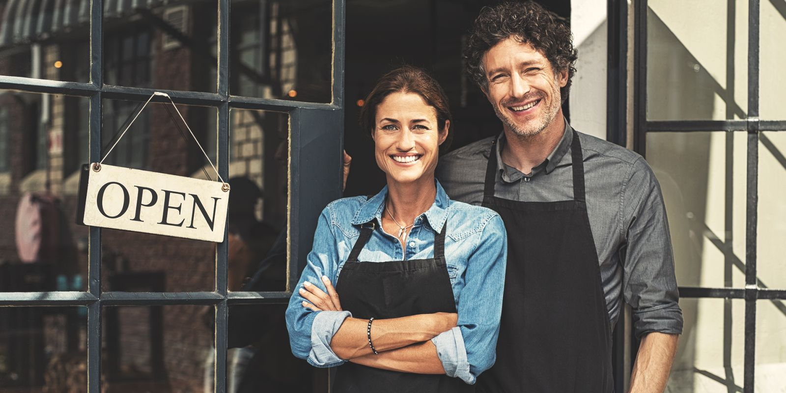 A picture of a man and woman stood in the door way of a shop with an open sign on the case study video production process page.
