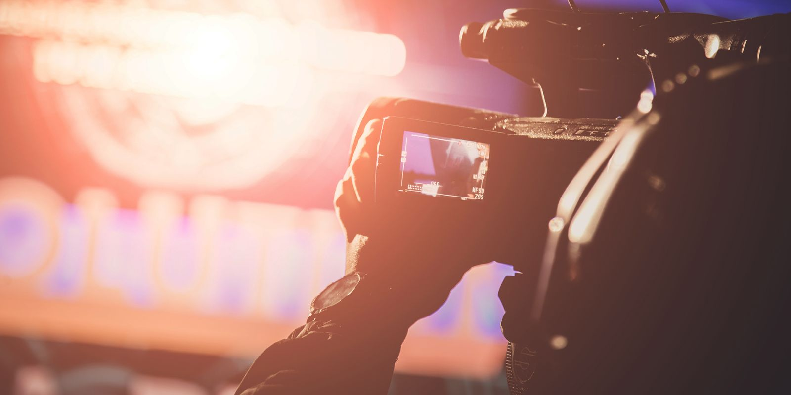 A picture of a large video camera filming something on stage with bright lights, on the conference video production page.