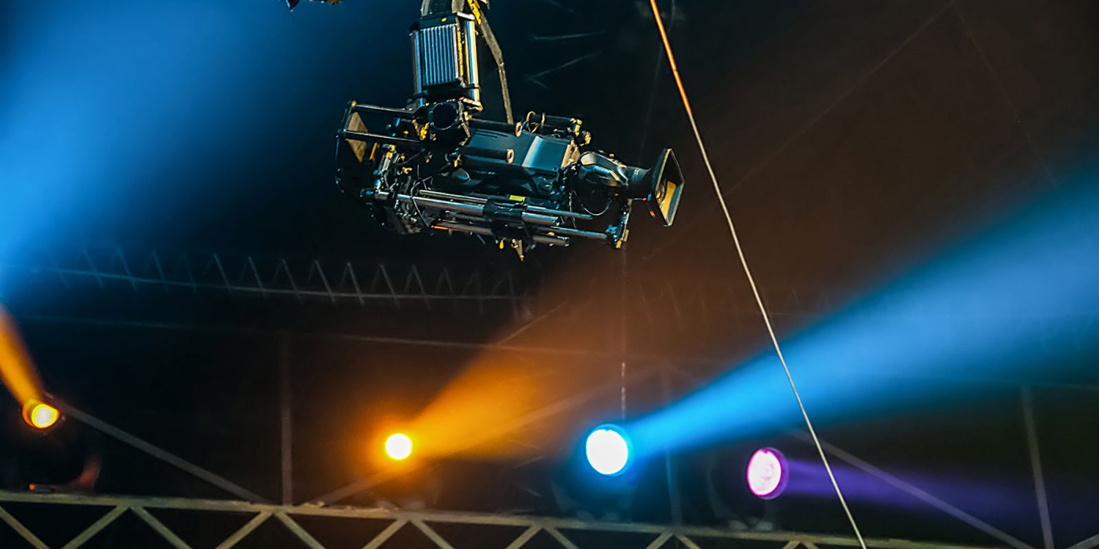 A picture of a drone in the air, with a stage set in the back ground, on the event video production page.