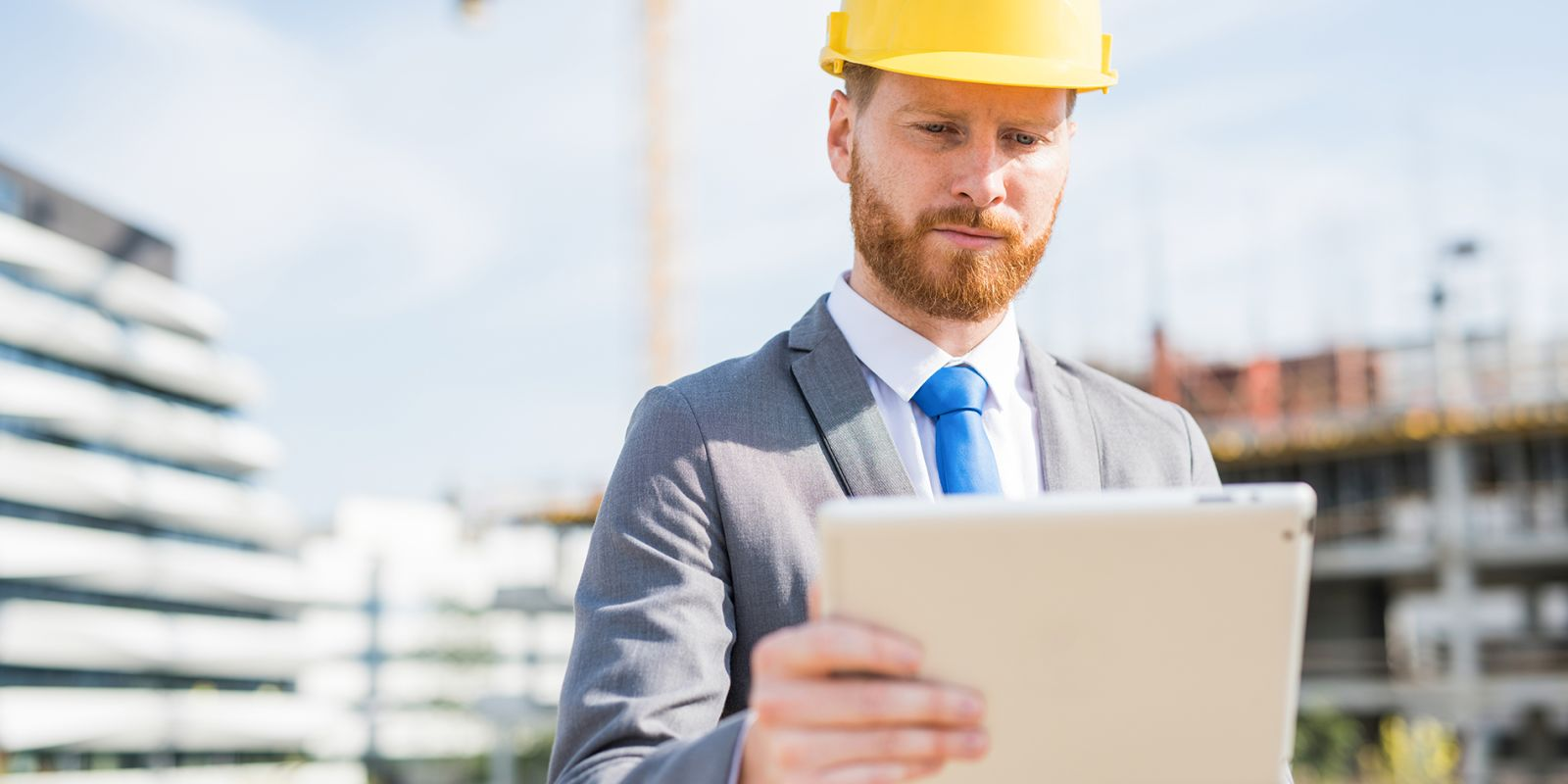 Picture of a man with a hard hat on looking at an iPad on a construction site on the health and safety video production page.
