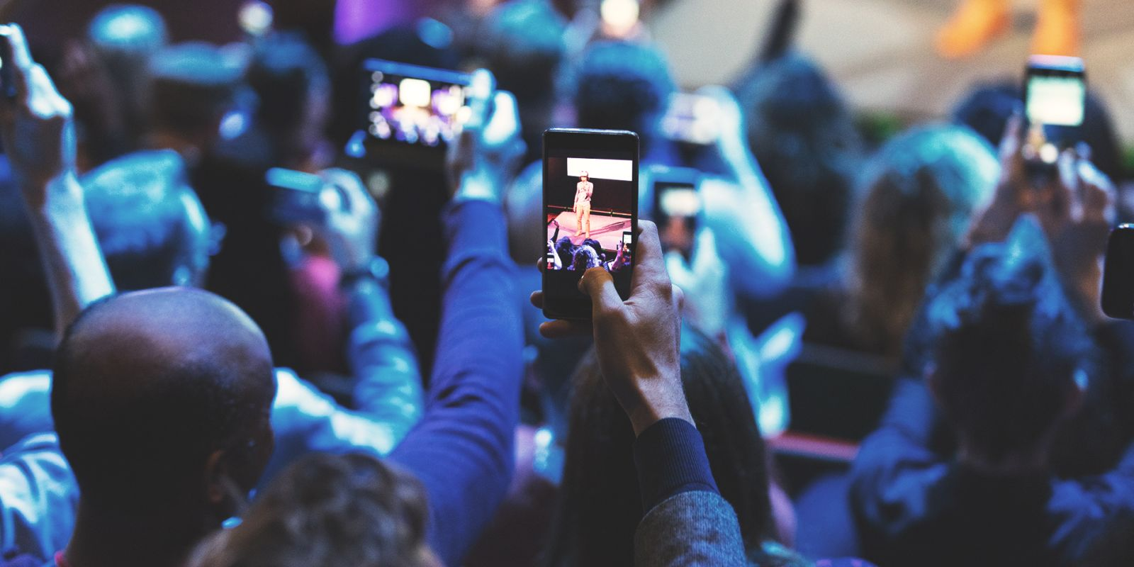 A picture of an audience holding up their phones and filming someone on stage on the promotional video production page.
