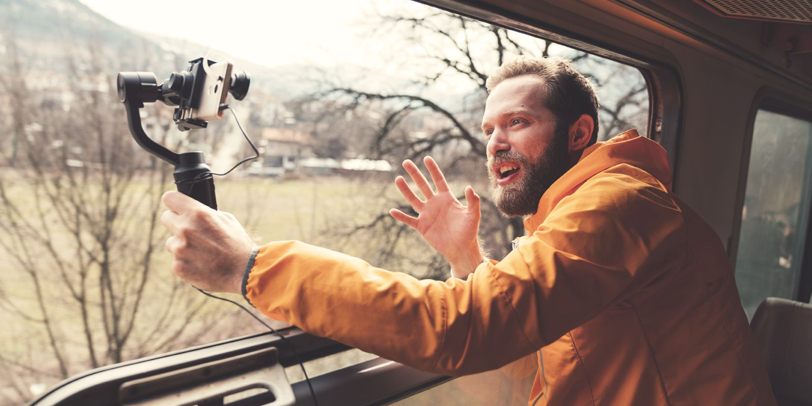 A picture of a man looking out the window of a train whilst filming himself on a phone on the social media video production page.
