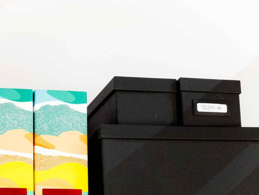 pile of black shoe box next to wall