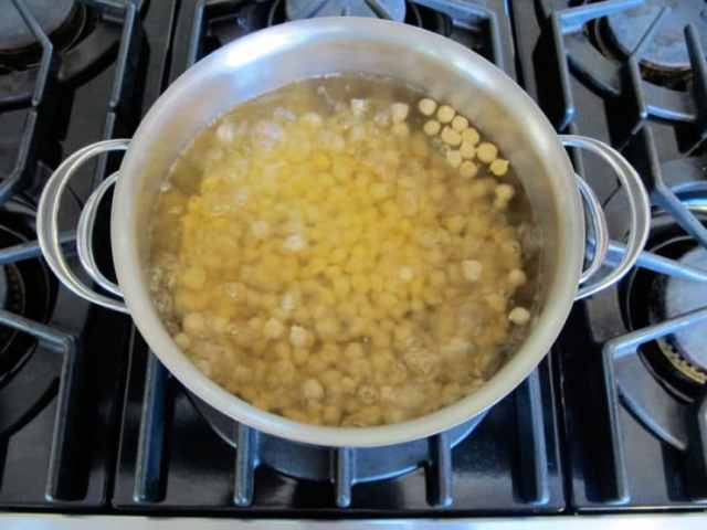 Boiling chickpeas in a large pot on stovetop for quick soaking.