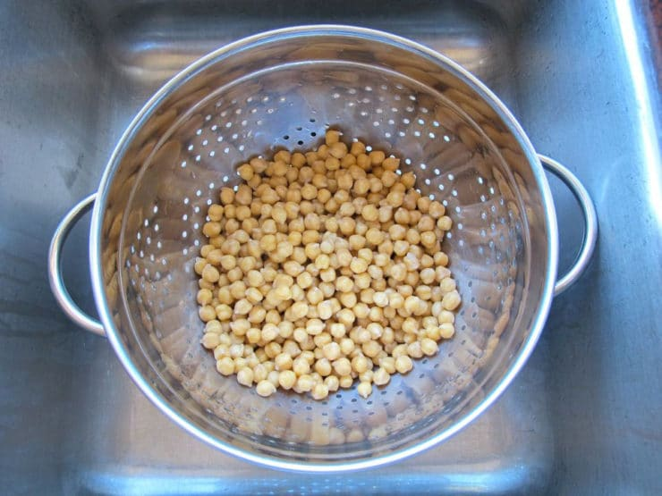 Draining chickpeas in colander in sink after soaking.