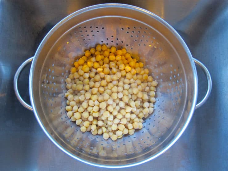 Cooked chickpeas drained in colander over sink.