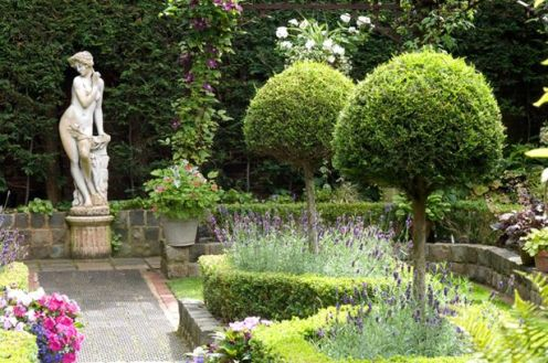 Secluded parterre garden with paths and walls made from reclaimed cobbles