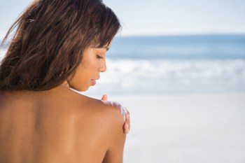 Woman on the beach applying sunscreen on her shoulder.