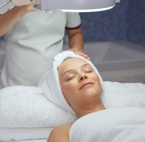 happy woman lying on massage table, keeping her eyes closed, relaxing after facial treatment
