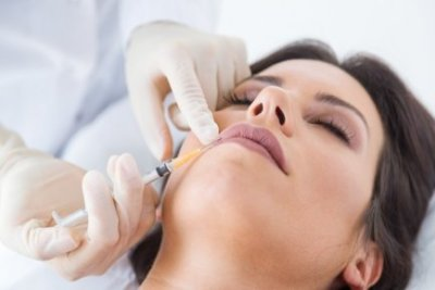 Portrait of beautiful young woman getting botox cosmetic injection in her face.