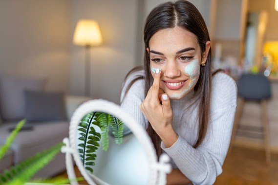 So beautiful. Close-up of girl with beauty mask on her face looking in mirror. Beautiful Woman Applying Natural Homemade Facial Mask at home. Spa and Skin care concept