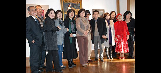 The 12 artists and reception guests stand for a group photo.