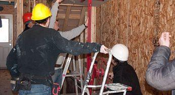 Habitat workers and volunteers put up drywall