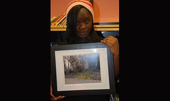 "Priscilla Y. holding her photo, ""Defy the Odds"" which expresses the idea that there is always hope even in the worst situation."