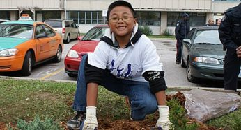 Chris, son of a Toronto Anti-Violence Intervention Strategy (TAVIS) team officer, gets his hands dirty spreading mulch Saturday. Kids from the building at 3181 Eglinton Ave. E. joined members of TAVIS to beautify the building's courtyard, have some fun and build relationships.