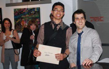 Artist Glenn Bernabe receives his award for his pastel on paper artwork.